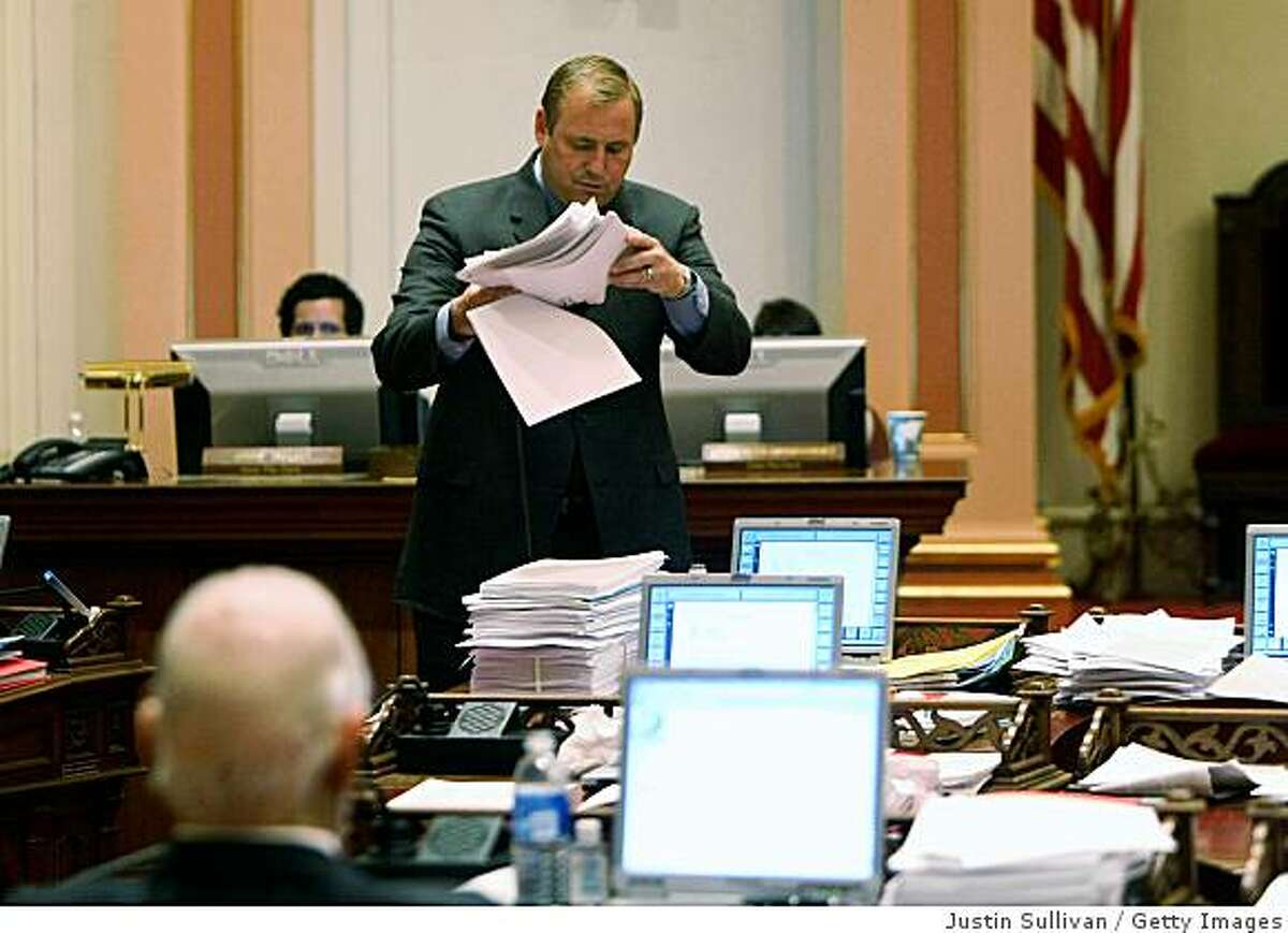 SACRAMENTO, CA - FEBRUARY 17: California State Sen. Jeff Denham (R-Atwater) picks up a pile of budget papers during a session of the California State Senate February 17, 2009 in Sacramento, California. The California legislature is preaparing for a long night as they work to hammer out a State budget to avoid thousands of layoffs of State workers and briging state funded construction projects to a halt. (Photo by Justin Sullivan/Getty Images)