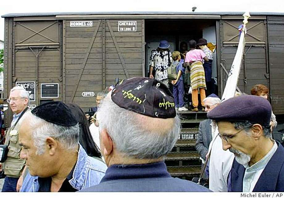 In this Aug. 20, 2001, file photo French Holocaust survivors gather at the site of the former Drancy detention camp, north of Paris, to mark the 60th anniversary of the camp's opening. The wagon is part of the memorial site. France's top judicial body on Monday recognized the French government's responsibility for the deportation of Jews during World War II, the clearest such recognition of the state's role in the Holocaust. Photo: Michel Euler, AP