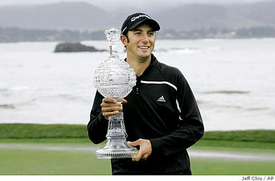 Dustin Johnson holds up his trophy on the 18th green of Pebble Beach golf links after winning the AT&T  Pebble Beach National Pro-Am golf tournament in Pebble Beach, Calif., Monday, Feb. 16, 2009. The tournament ended after 54 holes due to weather conditions. (AP Photo/Jeff Chiu) Photo: Jeff Chiu, AP
