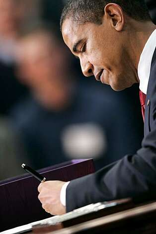 President Barack Obama signs the $787 billion economic stimulus bill at the Denver Museum of Nature and Science in Denver on Tuesday, Feb. 17, 2009. Photo: Barry Gutierrez, Rocky Mountain News