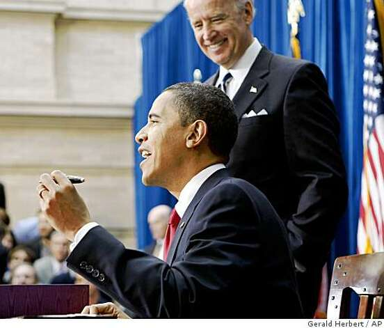 With Vice President Joe Biden looking on, President Barack Obama comments on the number of pens he has to use as he signs the American Recovery and Reinvestment Act,Tuesday, Feb. 17, 2009. Photo: Gerald Herbert, AP
