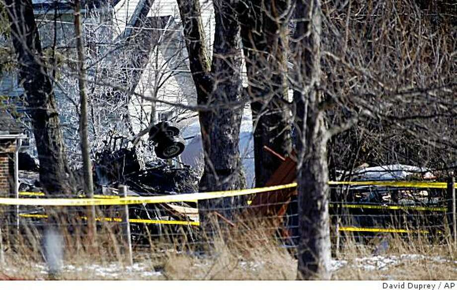 The wreckage of a Continental Connection Flight 3407 is seen from the backyard after it crashed into a house Thursday in Clarence Center, N.Y., Friday Feb. 13, 2009. (AP Photo/David Duprey) Photo: David Duprey, AP