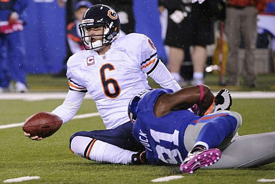 In this photo taken Oct. 3, 2010 in East Rutherford, N.J., Chicago Bears quarterback Jay Cutler is sacked by New York Giants defensive end Justin Tuck, during the second quarter of an NFL football game. Cutler took several hard hits while getting sacked nine times in the game and suffering a concussion. Photo: Bill Kostroun, AP