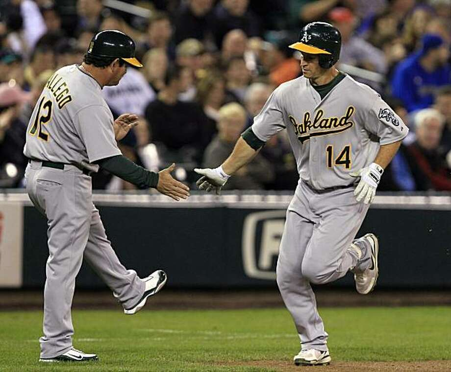 Oakland Athletics' Mark Ellis (14) is congratulated by third base coach Mike Gallego on his home run against the Seattle Mariners in the fourth inning during a baseball game Saturday, Oct. 2, 2010, in Seattle. Photo: Elaine Thompson, AP