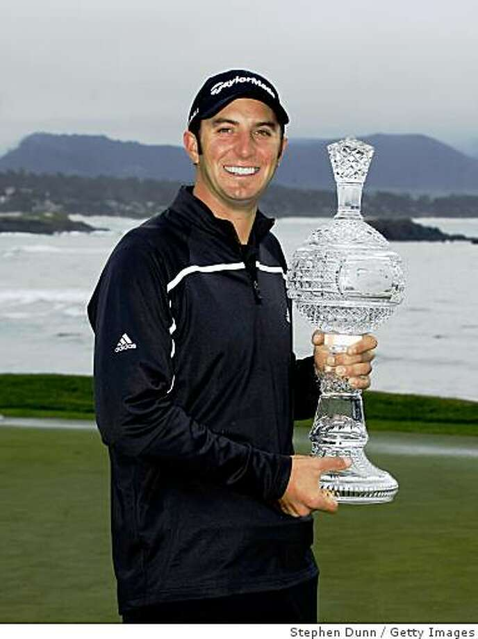 PEBBLE BEACH, CA - FEBRUARY 16:  Dustin Johnson poses with the trophy on th e18th green at Pebble Beach Golf Links after cancellation of the final round of the the AT&T Pebble Beach National Pro-Am on February 16, 2009 in Pebble Beach, California.  (Photo by Stephen Dunn/Getty Images) Photo: Stephen Dunn, Getty Images