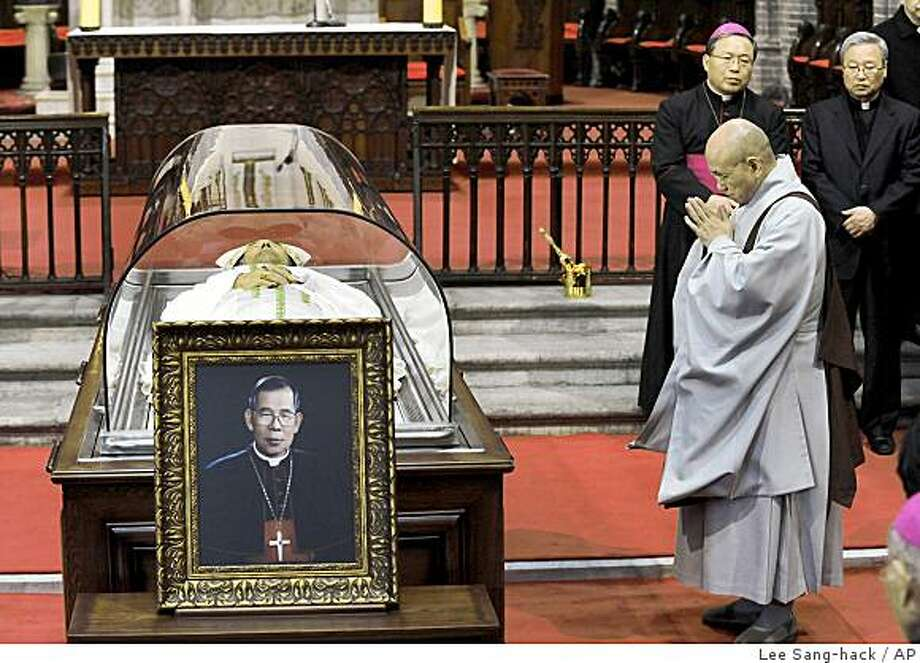An unidentified Buddhist monk prays beside a body of Cardinal Stephen Kim Sou-hwan at a Catholic Church in Seoul, South Korea, Monday, Feb. 16, 2009. Kim, a tireless advocate for democracy who opposed South Korea's military dictatorships, died Monday, a church official said.  Kim was outspoken in calling for the country's democratization and in 1987 allowed anti-government student activists to take refuge in Seoul's main cathedral. South Korea was ruled by military strongmen from 1961 until the late 1980s.(AP Photo/Yonhap, Lee Sang-hack)  ** KOREA OUT ** Photo: Lee Sang-hack, AP