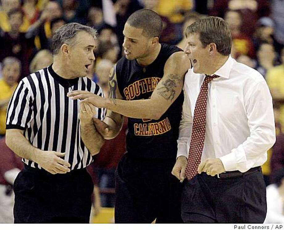 Southern California coach Tim Floyd, right, yells at official Dick Cartmell, left, as Southern California guard Dwight Lewis, center, separates the two during the second half of an NCAA college basketball game against Arizona State on Sunday, Feb. 15, 2009, in Tempe, Ariz. Floyd was ejected from the game. Arizona State won 65-53. (AP Photo/Paul Connors) Photo: Paul Connors, AP