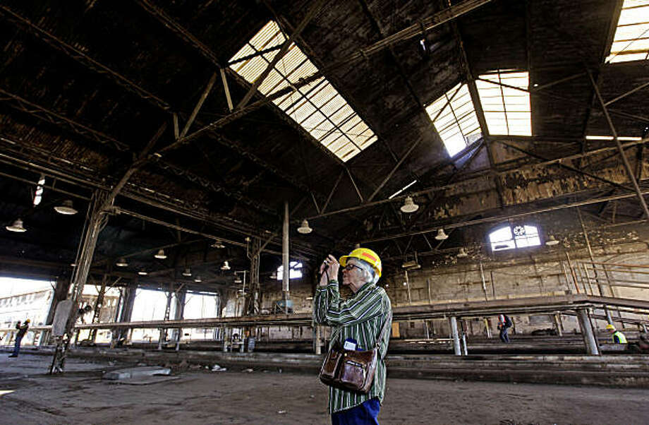 Joyce Roy, a transit historian from Oakland, takes photographs inside the locomotive repair shop as she joins railroad buffs and fellow historians in West Oakland, Calif. on Thursday, Sept. 23, 2010, for one last glimpse of the shop. Union Pacific is scheduled to begin demolition of the building, which was built in 1874. Photo: Michael Macor, The Chronicle