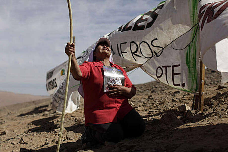 Aurelia Navarro, a volunteer missionary, prays during a small ceremony marking the 60 days since miners became trapped in the San Jose Mine near Copiapo, Chile, Tuesday Oct. 5, 2010.  Chile's President Sebastian Pinera announced that his government is very close to pulling 33 miners to safety after they became trapped on Aug. 5 in the collapsed gold and copper mine. Photo: Dario Lopez-Mills, AP