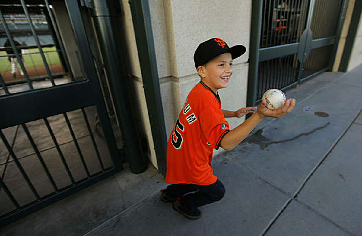 10-year-old Rod Cardoza, of San Jose, shows off a baseball from Ramon Ramirez, as he watched through the right field fence, the San Francisco Giants hold a batting practice at AT&T Ball Park, on Tuesday Oct. 4, 2010, in preparation for the National League Divisional Series which is set to get underway later this week.