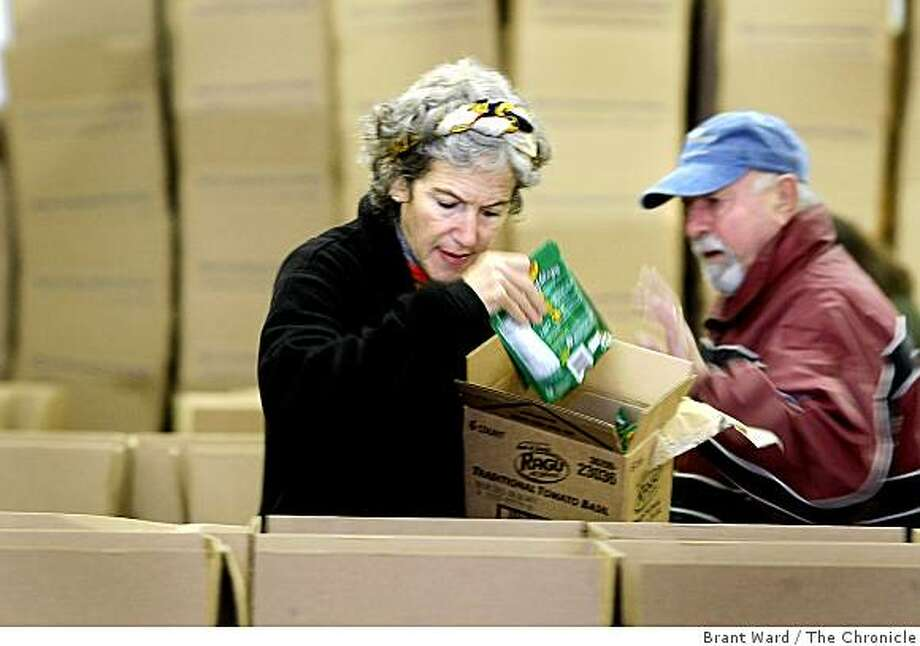 Suzanne Warner, left, and Hank Franzini were among about a dozen volunteers filling boxes for the needy in Novato. A group of volunteers gathered at the Marin County Community Food bank to pack food holiday boxes Tuesday, December 16, 2008. Photo: Brant Ward, The Chronicle