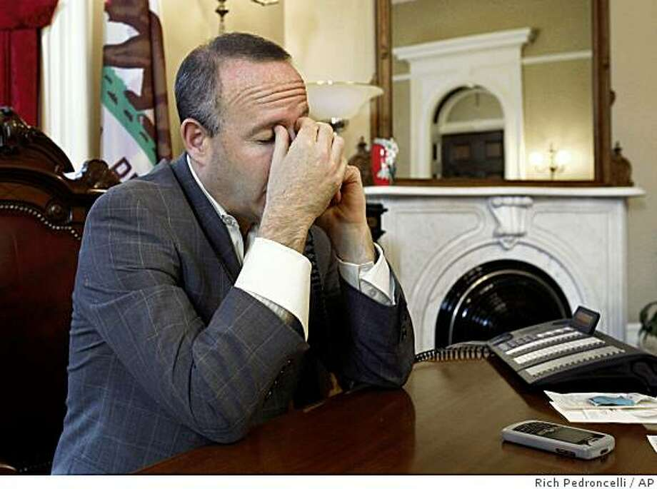 Stat Sen. President Pro Tem Darrrell Steinberg, D-Sacramento, rubs his eyes during a call to a lawmaker concerning the state budget at his Capitol office in Sacramento, Calif., Friday, Feb. 13, 2009.  Steinberg spent the day talking with members of the Senate about the vote on the state budget package that will be brought before both houses of the Legislature Saturday.(AP Photo/Rich Pedroncelli) Photo: Rich Pedroncelli, AP