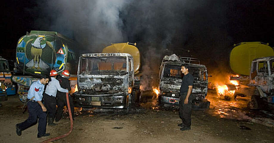 Pakistani fire fighters struggle to extinguish burning oil tankers after militants attacked a terminal in Rawalpindi, Pakistan, early Monday, Oct. 4, 2010.  Police say suspected militants have attacked and set on fire at least 20 oil tankers in Pakistan that were en route to NATO and US troops in Afghanistan. Photo: Anjum Naveed, AP