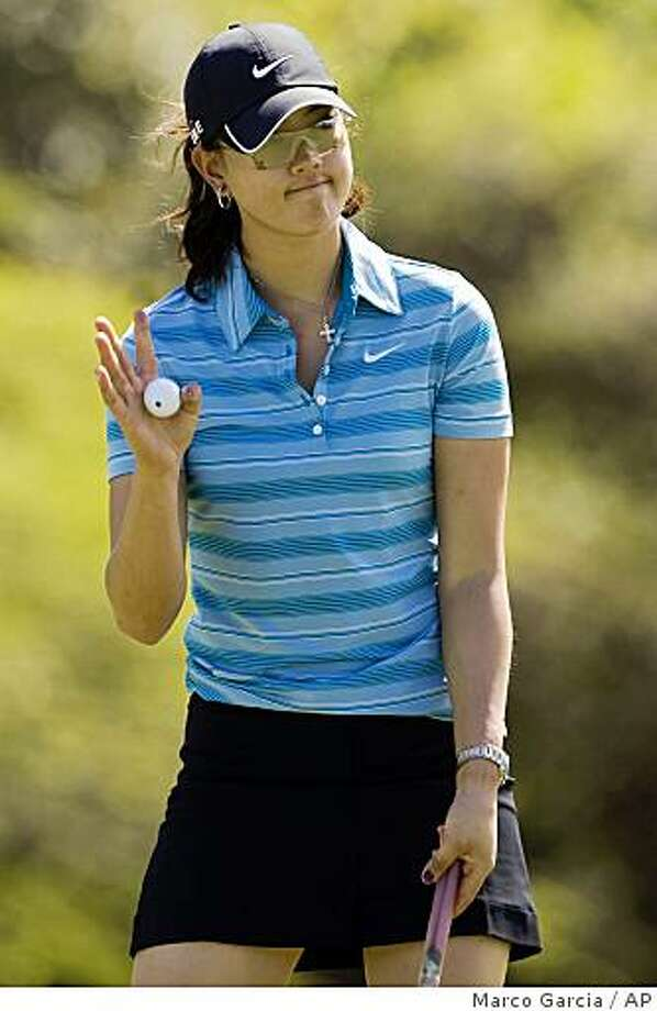 Michelle Wie waves to the gallery after making a par putt on the ninth green during the second round of the LPGA SBS Open golf tournament at the Turtle Bay Resort, Friday, Feb. 13, 2009 in Kahuku, Hawaii.(AP Photo/Marco Garcia) Photo: Marco Garcia, AP