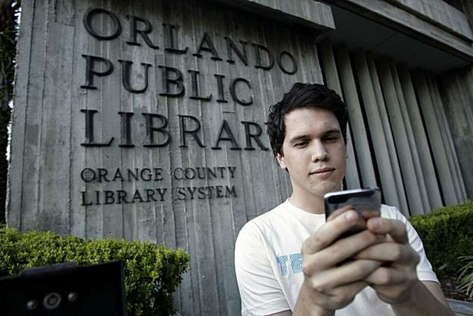 "Hillard Goodspeed uses an ipod application called  ""shake it"",  to find reading suggestions at the Orlando Public Library in Orlando, Fla., Wednesday, Sept. 1, 2010. Photo: John Raoux, AP"