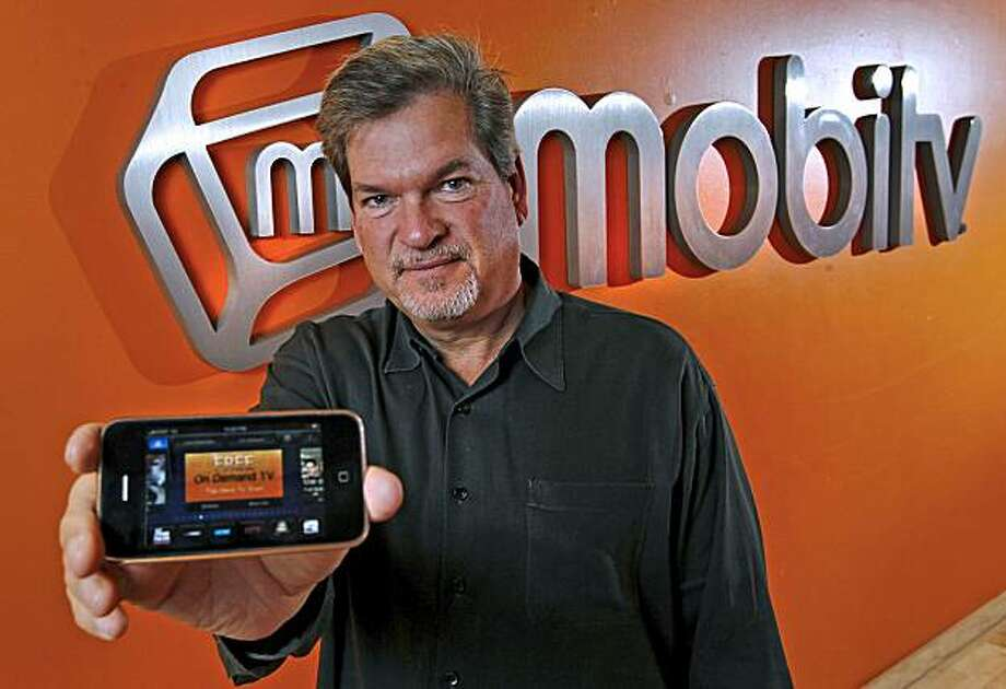 Charlie Nooney, chief executive officer of MobiTV Inc., holds an Apple iPhone that runs the MobiTV application as he poses in the lobby of the company's headquarters in Emeryville, California, U.S., on Thursday, Sept. 30, 2010. Founded in 1999, MobiTV has developed software that delivers sports, television shows, and news to more than 350 devices and is approaching $100 million in annual revenue. The company plans to introduce a new service to bring their technology into homes during the CTIA wireless industry conference. Photographer: Tony Avelar/Bloomberg *** Local Caption *** Charlie Nooney Photo: Tony Avelar, Bloomberg