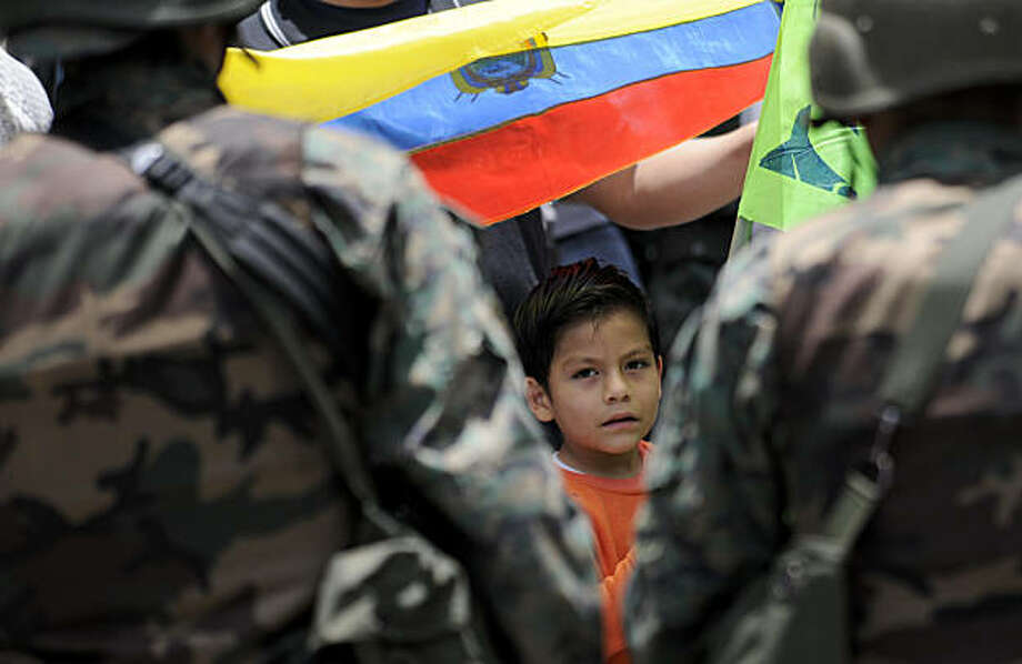 A boy, carrying an Ecuadorian flag, demonstrates in front of soldiers at the surroundings of the government palace in Quito, Ecuador, Friday, Oct. 1, 2010. Ecuador is under a state of siege, with the military in charge of public order, after soldiers rescued Ecuador's President Rafael Correa from a hospital where he'd been surrounded by police who roughed him up and tear-gassed him earlier. Photo: Patricio Realpe, AP