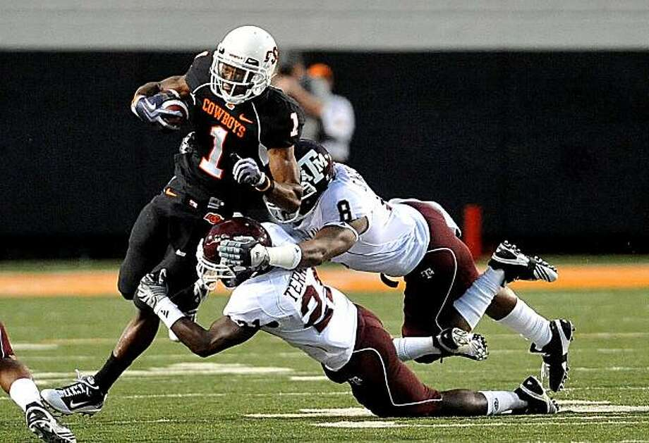 Oklahoma State running back Josephe Randie is tackled by Texas A&M's Steven Terrell and Garrick Williams during an NCAA college football game Thursday, Sept. 30, 2010, in Stillwater, Okla. Photo: Chelcey Adami, AP
