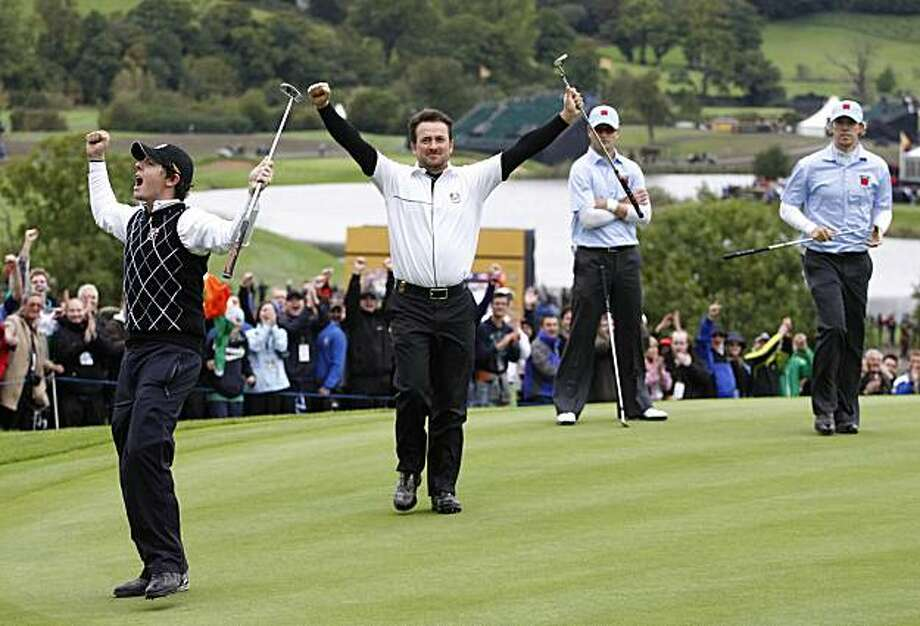 Europe's Rory McIlroy, left, and Graeme McDowell, second left, react after winning their match on the 17th green as U.S. team members Hunter Mahan, right, and Zach Johnson look on during the third day of the 2010 Ryder Cup golf tournament at the Celtic Manor Resort in Newport, Wales, Sunday, Oct.  3, 2010. Photo: Peter Morrison, AP