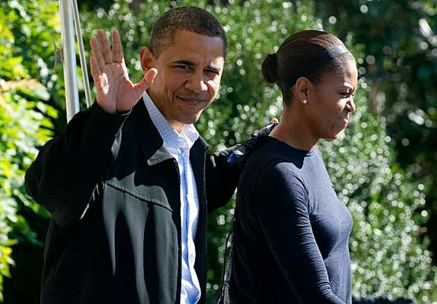 US President Barack Obama waves alongside First Lady Michelle Obama as they walk to Marine One prior to departing from the South Lawn of the White House in Washington, DC, October 2, 2010. The Obamas are traveling to Camp David, the presidential retreat in Maryland. Photo: Saul Loeb, AFP/Getty Images