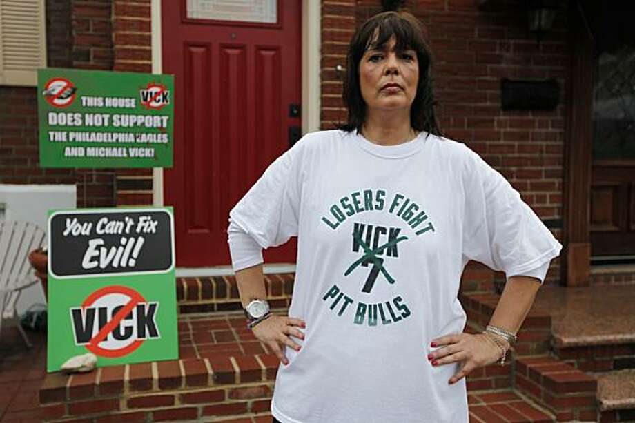 In this photo taken Sept. 30, 2010, Monica Caraffa poses for a photograph with signs in front of her home opposing Philadelphia Eagles quarterback Michael Vick, in Philadelphia. Despite his ascendancy to starting quarterback and several winning performances in that role, Vick has not won over many of the animal-loving Eagles fans who were the most incensed when he was signed last year. Photo: Matt Rourke, AP