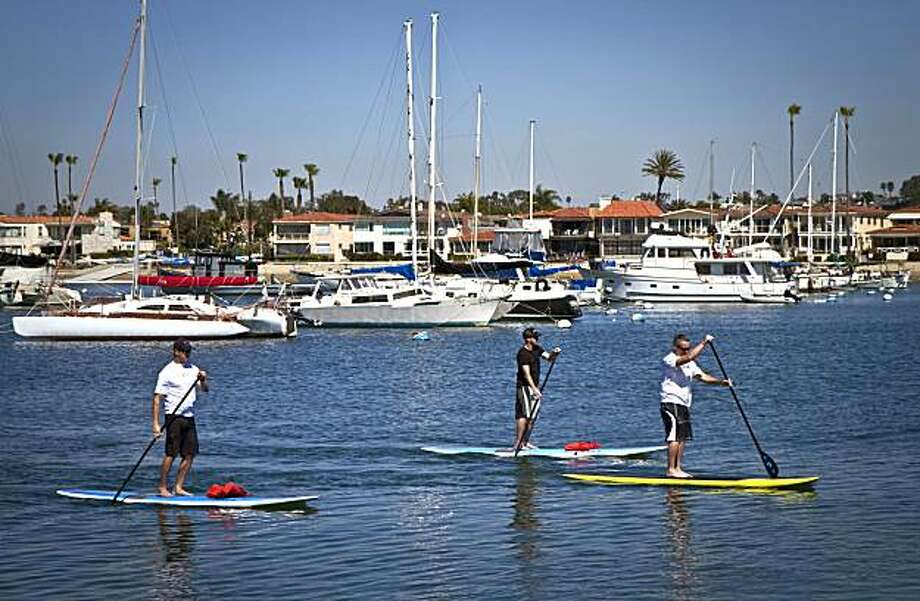 Stand-up paddle-boarders glide across Newport Harbor, which is offers the kind of flat water suitable for the sport. Photo: Visit Newport Beach Inc.