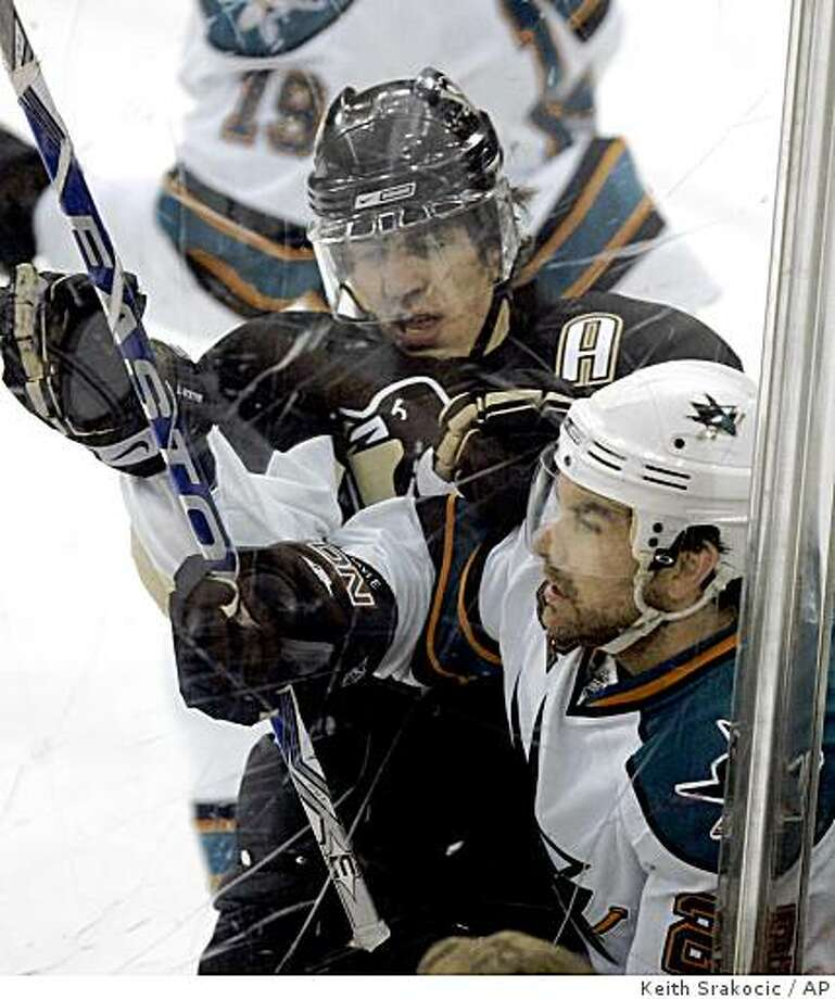 Pittsburgh Penguins' Evgeni Malkin, left, of Russia, battles along the boards with San Jose Skarks' Dan Boyle in the first period of an NHL hockey game in Pittsburgh on Wednesday, Feb. 11, 2009. (AP Photo/Keith Srakocic) Photo: Keith Srakocic, AP