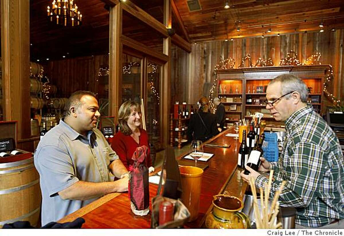 Julie Banerjea (middle) and her husband, Sam Banerjea (left) at the Lambert Bridge winery taste room with Dean Agostinelli (right) helping them behind the counter in Healdsburg, Calif., on January 23, 2009.