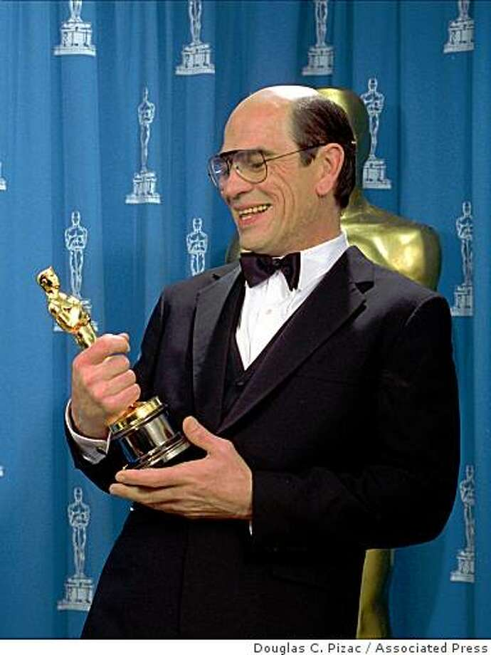 "Tommy Lee Jones admires the Oscar he just received for best supporting actor for his role in the film ""The Fugitive,"" at the 66th annual Academy Awards in Los Angeles Monday, March 21, 1994. Photo: Douglas C. Pizac, AP"