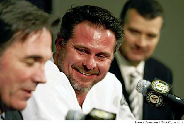 Oakland Athletics' Jason Giambi center looks on as Athletics General Manager Billy Beane takes questions from the media at a news conference in Oakland, Calif., Wednesday, Jan. 7, 2009. Giambi and the Athletics finalized a one-year contract with an option Wednesday, bringing the free-agent home to Oakland. Photo: Lance Iversen, The Chronicle