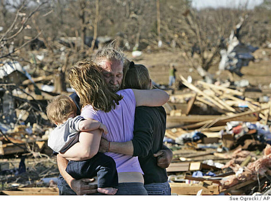 Dennis Parker, center, is embraced by his daughter Dondria Hickman, left, who holds his grandson Benjamin Bryce Hickman, and friend Barbie Vaughn, right, at the site of his demolished trailer home in Lone Grove, Okla., Wednesday, Feb. 11, 2009. Parker's home was destroyed by a tornado Tuesday night.(AP Photo/Sue Ogrocki) Photo: Sue Ogrocki, AP