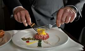 Blake Tippett, manager of Bix restaurant, mixes the egg with the cropped New York steak as he prepares steak tartare, Monday Sept. 20, 2010, in San Francisco, Calif.