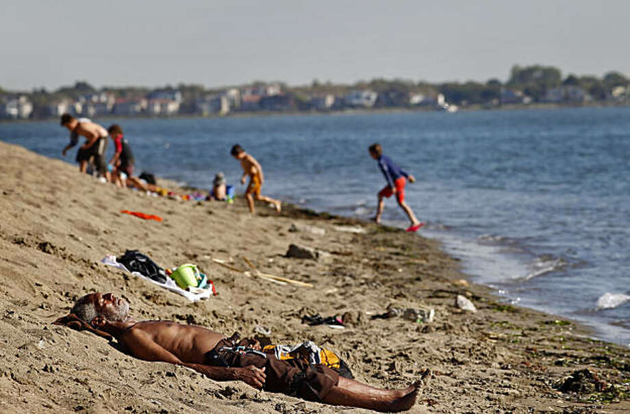 Mavin Dixon from Oakland, lays in the sun, Tuesday Sept. 28, 2010, at the Crown Memorial State Beach in Alameda, Calif. Beach-goers in Alameda began reporting itchy, pustulent rashes primarily on their legs and feet. In the current issue of Emerging InfecMavin Dixon from Oakland, lays in the sun, Tuesday Sept. 28, 2010, at the Crown Memorial State Beach in Alameda, Calif. Beach-goers in Alameda began reporting itchy, pustulent rashes primarily on their legs and feet. In the current issue of Emerging Infectious Diseases a team of researchers reports that the rash is caused by a newly discovered schistosome parasite carried by a recently arrived Japanese snail. Photo: Lacy Atkins, The Chronicle