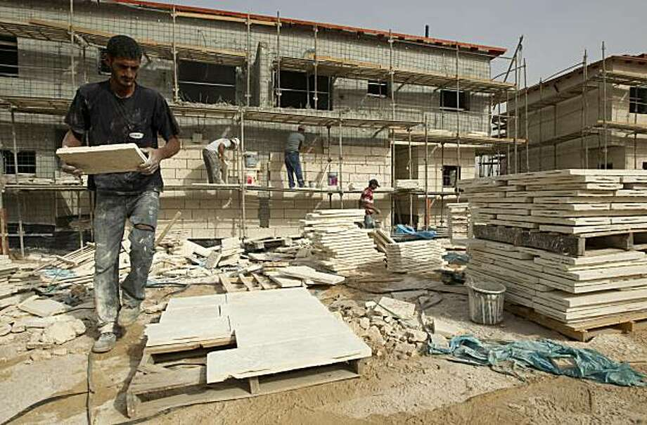 Palestinian labourers work at the construction site of new houses in the West Bank Jewish settlement of Ariel, which was established in 1978 and houses some 16,716 people, on September 26, 2010, hours before the end of a freeze on settlement construction. Photo: Jack Guez, AFP/Getty Images
