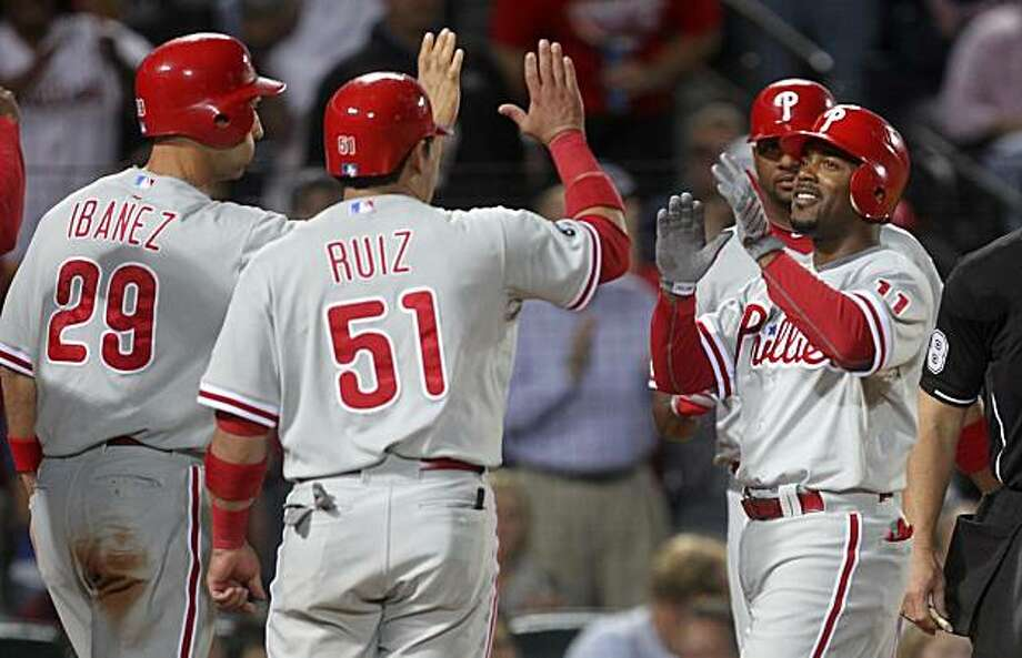 Philadelphia Phillies shortstop Jimmy Rollins, right, celebrates with teammates  Raul Ibanez (29), and Carlos Ruiz (51) after hitting a grand slam in the sixth inning  of a baseball game against the Atlanta Braves Friday, Oct. 1, 2010 in Atlanta. Photo: John Bazemore, AP