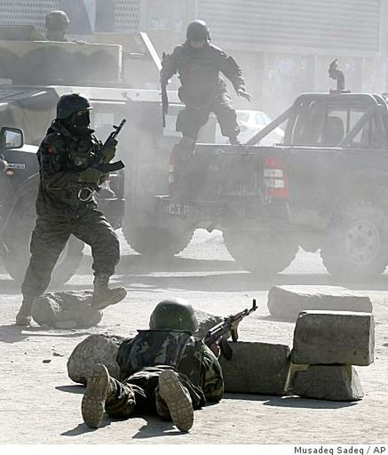 ** ALTERNATIVE CROP OF KAB101 **Afghan security forces run for the site of Afghan Justice Ministry following an attack in Kabul, Afghanistan on Wednesday, Feb. 11, 2009. Assailants, some wearing suicide vests, attacked the Justice Ministry and another government building in Afghanistan's capital Wednesday, causing multiple deaths and forcing workers to flee from building windows. The Taliban claimed responsibility for the attacks. (AP Photo/Musadeq Sadeq) Photo: Musadeq Sadeq, AP
