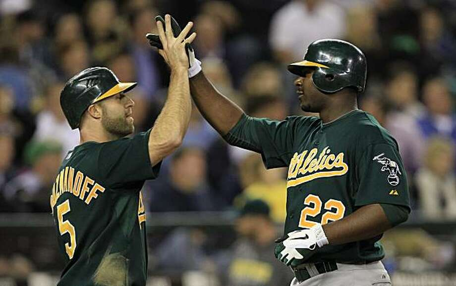 Oakland Athletics' Chris Carter (22) is met at home by Kevin Kouzmanoff on Carter's two-run home run against the Seattle Mariners in the sixth inning during a baseball game Thursday, Sept. 30, 2010, in Seattle. Photo: Elaine Thompson, AP