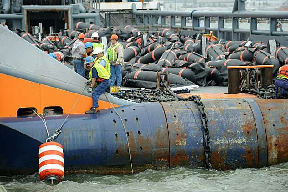 (FILES)Men position a bouy on board a boat with oil boom barriers from the US Navy that is expected to stop the spread of oil from the BP Deepwater Horizon platform disaster in this May 1, 2010 file photo at the main port in Gulfport, Mississippi. US authorities announced new safety rules on September 30, 2010 for offshore oil and gas drilling, a move aimed at preventing a recurrence of the disastrous Deepwater Horizon accident earlier this year.The Interior Department said two new rules will toughen requirements for safety equipment, well control systems, and blowout prevention practices on offshore oil and gas operations; they also seek to address workplace safety by reducing the risk of human error. Photo: Stan Honda, AFP/Getty Images