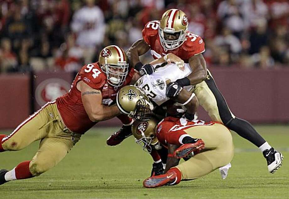 New Orleans Saints running back Pierre Thomas (23) is stopped by San Francisco 49ers defensive tackle Justin Smith (94), safety Michael Lewis (32) and safety Reggie Smith, bottom, in the third quarter of an NFL football game in San Francisco, Monday, Sept. 20, 2010. Photo: Marcio Jose Sanchez, AP