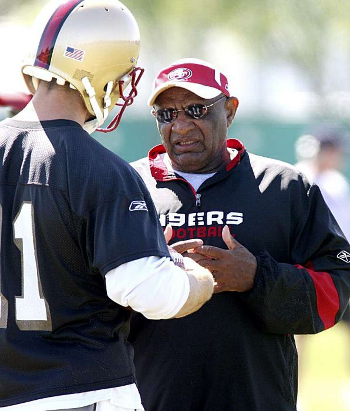San Francisco 49ers' quarterback Alex Smith, left, has a chat with offensive coordinator Jimmy Raye, at 49ers minicamp, Friday, March 20, 2009 in Santa Clara, Calif.