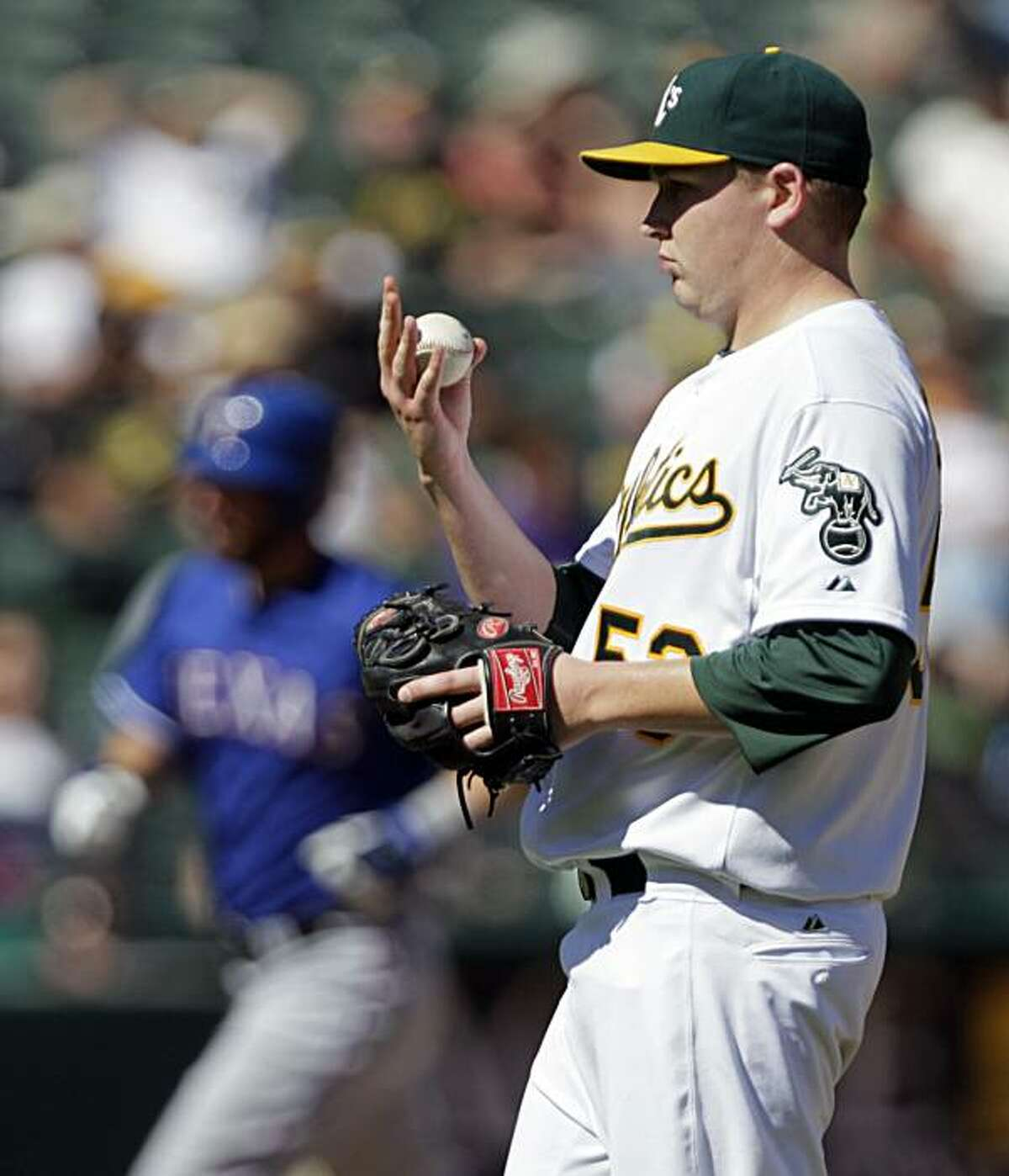Oakland Athletics' Trevor Cahill, right, regroups as Texas Rangers' Jeff Francoeur, left, runs the bases after hitting a home run during the fourth inning of a baseball game Sunday, Sept. 26, 2010, in Oakland, Calif.