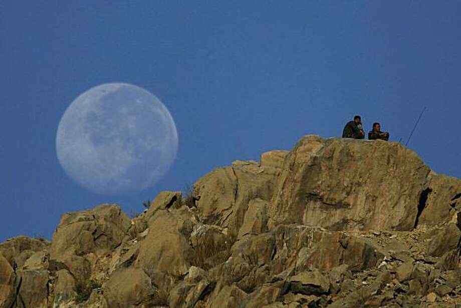 Afghan soldiers keep watch as the moon rises over a ridge during operation Spear Tackle 2 in Surobi district on September 26, 2010. Most of France's 3,500 soldiers, who are part of a NATO-led multinational force fighting the Taliban inside Afghanistan, are based in districts around Kabul. Photo: Joel Saget, AFP/Getty Images