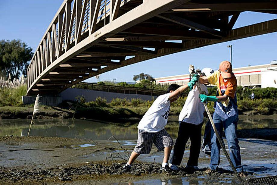 From right, Sean Vernon, Daniel Jun, Justin Chan, all 12, use a piece of wood that they found to dig a big piece of garbage out of the dirt at the water's edge at Save the Bay's Colma Creek location which attracted approximately 200 volunteers that picked up all kinds of trash in South San Francisco, Calif., on Saturday, September 25, 2010. Photo: Chad Ziemendorf, The Chronicle