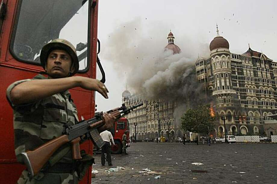 FILE - In this Nov. 29, 2008 file photo, an Indian soldier takes cover as the Taj Mahal hotel burns during gun battle between Indian military and militants inside the hotel in Mumbai, India.  European security officials said Wednesday Sept. 29, 2010, a terror plot to wage Mumbai-style shooting sprees or other low-budget attacks in Britain, France and Germany is still active and that sites in Pakistan _ where the threat was intercepted _ are being targeted for al-Qaida operatives. Photo: David Guttenfelder, AP