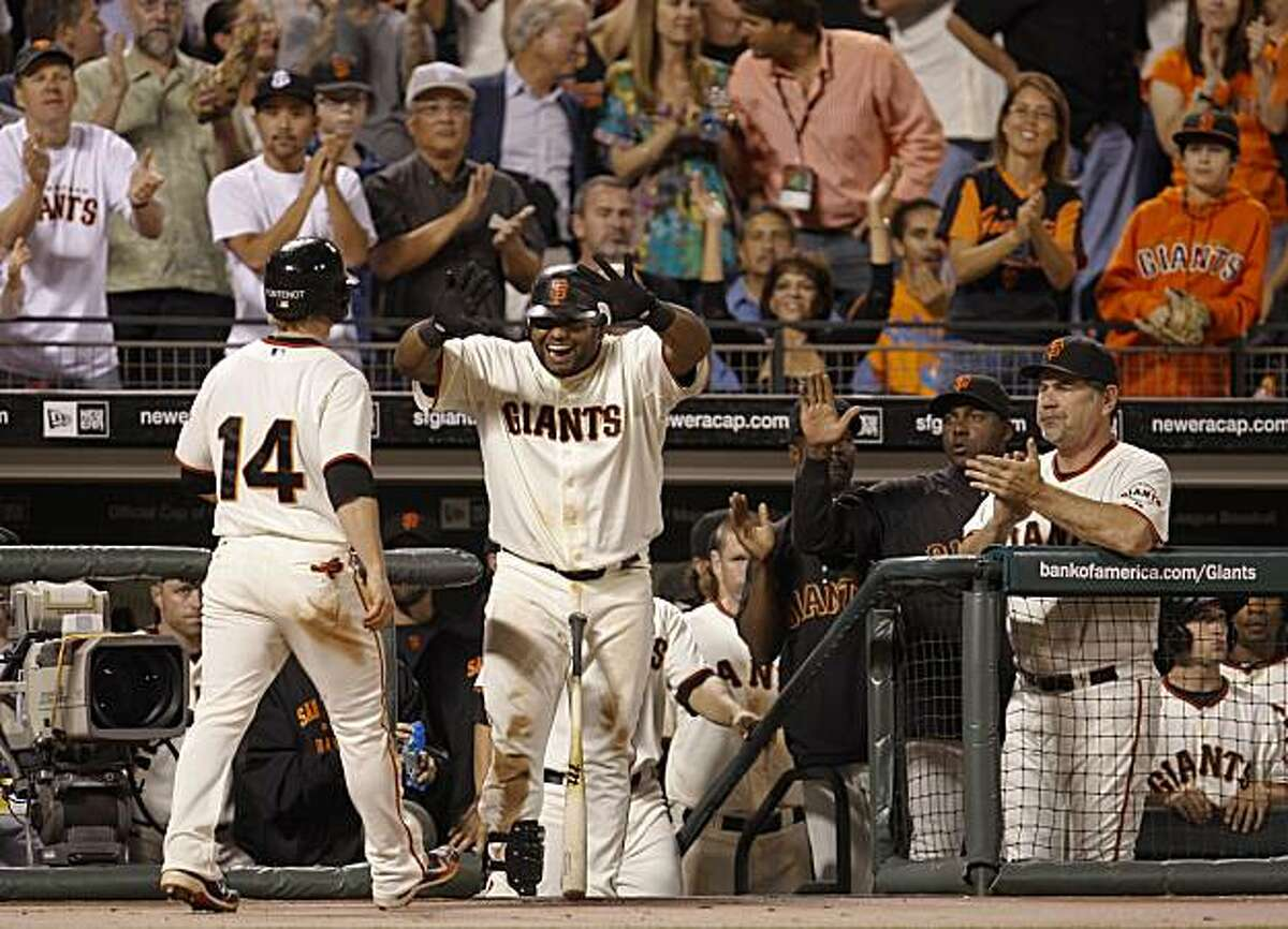 Mike Fontenot is greeted by Pablo Sandoval after he scored on a Pat Burrell single in the seventh inning to make it 4-2 Giants on Tuesday.
