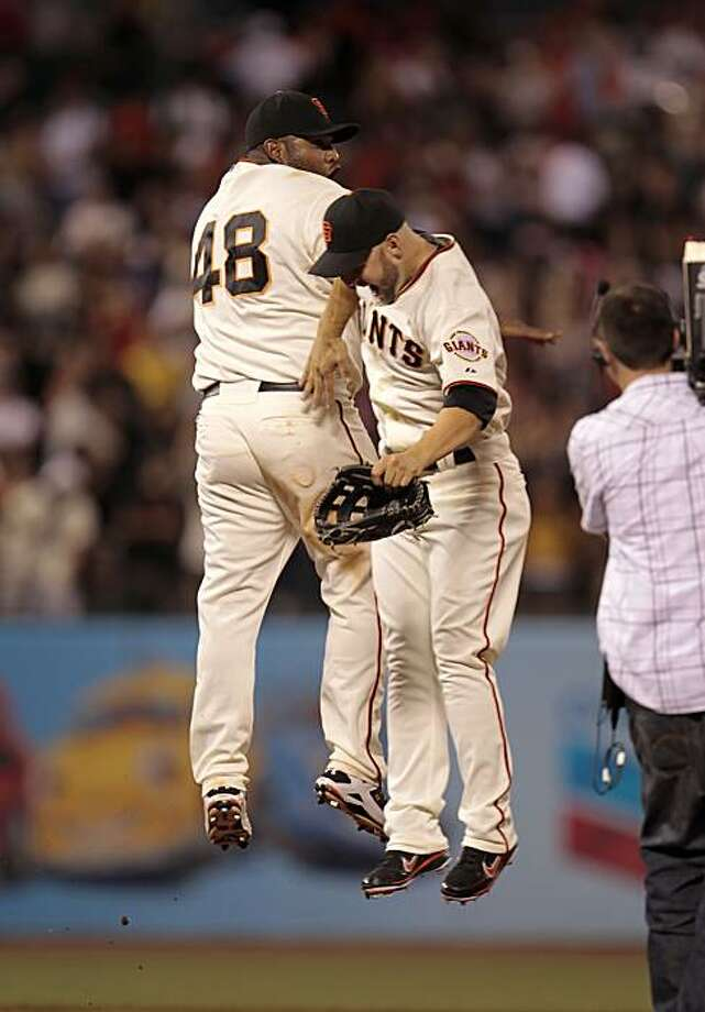 Pablo Sandoval and Cody Ross go airborne as they celebrate the Giants' win over the Diamondbacks at AT&T Park on Tuesday. Photo: Michael Macor, The Chronicle