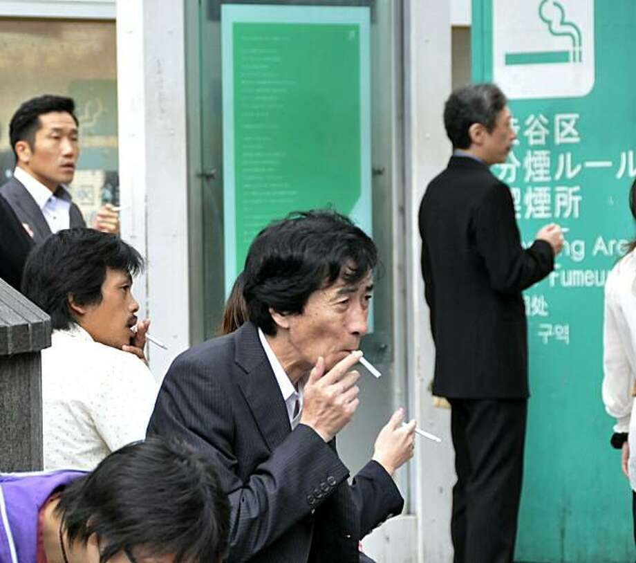 People smoke cigarettes at a smoking area in Tokyo on september 29, 2010.  Smokers in Japan are flocking to stock up on cigarettes, even by stealing them, or struggling to kick the habit ahead of a record tobacco price increase on October 1. Photo: Yoshikazu Tsuno, AFP/Getty Images