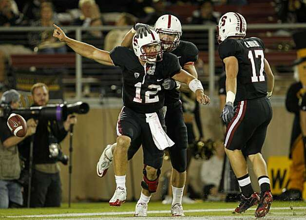 Stanford's quarterback, Andrew Luck, (12) celebrates his 52 yard touchdown run in the second quarter with teammates, Coby fleener, (82) and Griff Whelan, (17), as the Stanford Cardinal takes on Wake Forest in college football action at Stanford Stadium in Palo Alto, Ca. on Saturday Sept. 18, 2010. Photo: Michael Macor, The Chronicle
