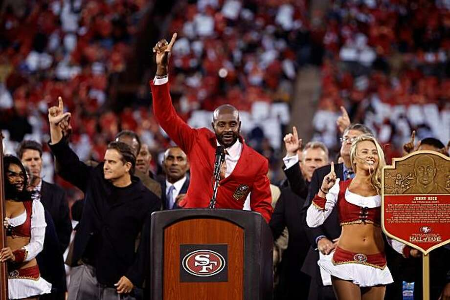 Jerry Rice raises his hand to the sky to honor his former coach Bill Walsh as Rice is honored at halftime and his jersey is retired at Candlestick Park in San Francisco on Monday. Photo: Paul Chinn, The Chronicle
