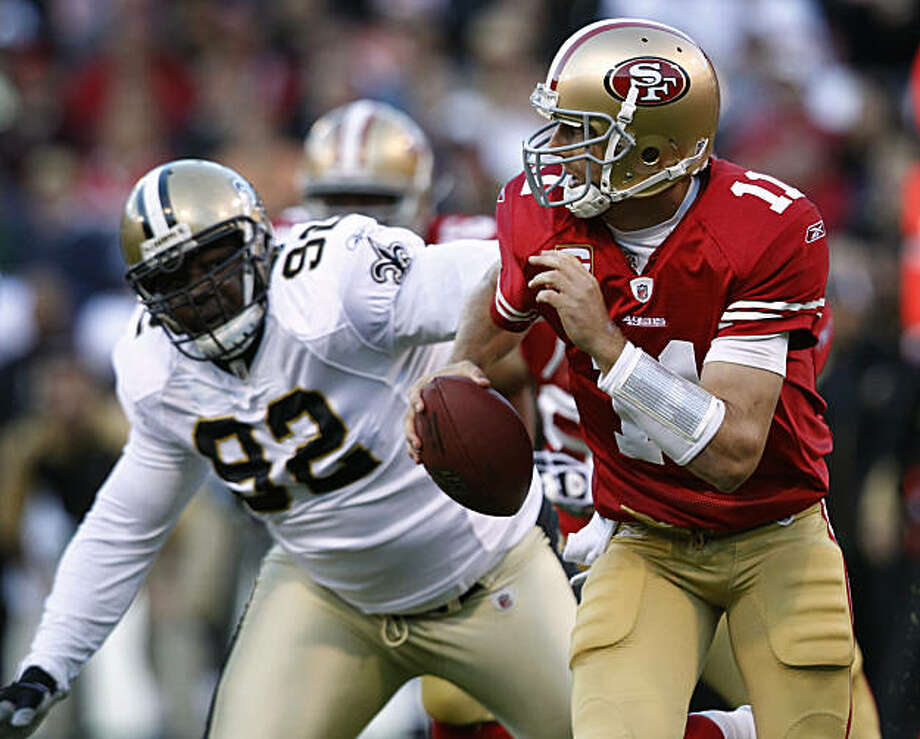 Quarterback Alex Smith eludes defensive tackle Remi Ayodele during the San Francisco 49ers and New Orleans Saints game at Candlestick Park in San Francisco on Monday. Photo: Paul Chinn, The Chronicle